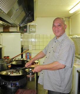Wing Lau bereitet das Reisgericht im großen Wok zu.