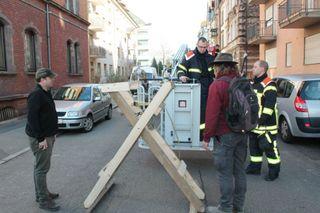 Helfer und Feuerwehr beratschlagen, wie sie Gestell und Nest auf das Dach bekommen.