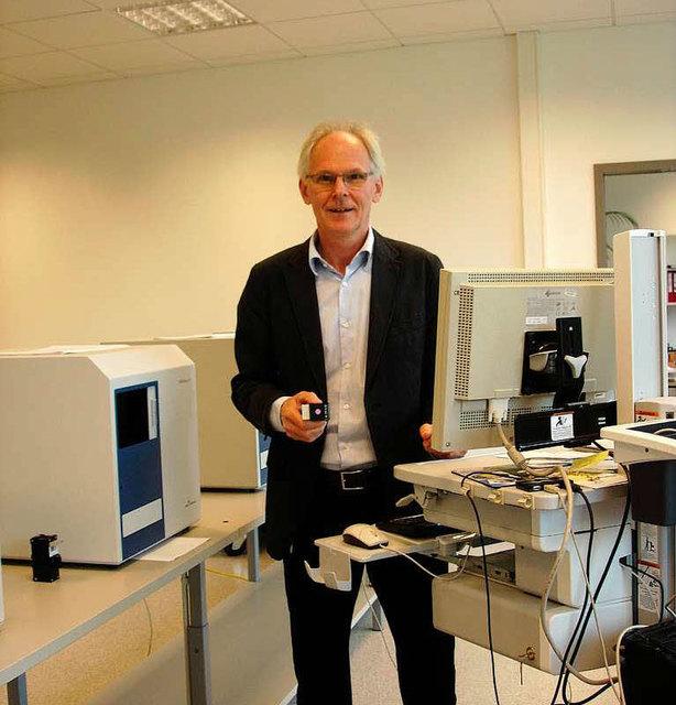 Geschäftsführer Thomas Räbiger inmitten der Mikroplatten-Lesegeräte.