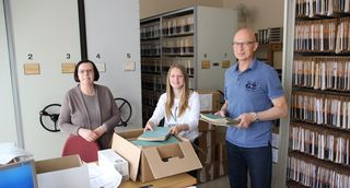 Für den Transport zum Landesgrundbuchzentralarchiv in Kornwestheim werden die Akten verpackt (von links): Helga Peter, Auszubildende Jana Förger und Ratschreiber Dieter Erk.