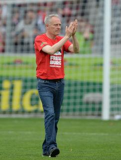 Freiburgs Trainer Christian Streich feiert mit den Fans.