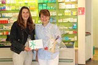 Apothekerin Doris Löweke (r.) übergibt Claudia Gebauer, der Tochter der Gewinnerin, stellvertretend den Preis.