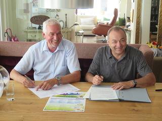 Jürgen Nowak, Vorsitzender des Gewerbevereins Oberwolfach, und Reinhold Waidele, Vorsitzender des Gewerbevereins Wolfach bei der Unterzeichnung der Kooperation