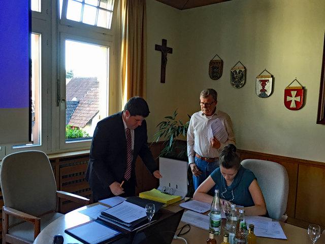 Bürgermeister Andreas König unterschreibt die Empfangsbestätigung der von Wolfgang Butz überreichten Unterschriftenliste.
