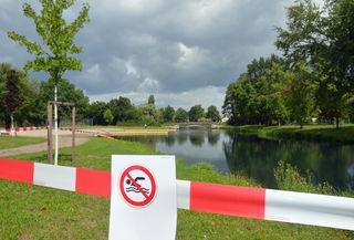 Rotweißes Flatterband rund um den See soll die Schwimmer abhalten ins Wasser zu gehen.