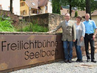 Bürgermeister Thomas Schäfer mit Daniela Armbruster und Pascal Weber vom Orga-Team der Freilichtspiele (von links) vor dem neuen Schild im Klostergarten Seelbach.