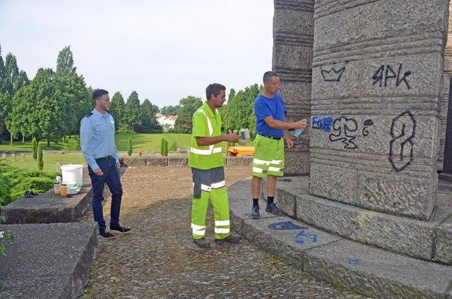 Nico Tim Glöckner begutachtet das besprühte Kriegerdenkmal, während die Betriebshofmitarbeiter damit beginnen, die Graffitis zu entfernen.