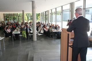 Oberbürgermeister Wolfgang G. Müller während seiner Ansprache über die Schulter geschaut: Die Mensa ist mit Raumteilern für viele Zwecke verwendbar.