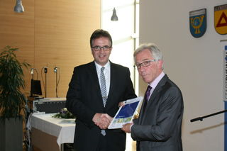 Feierlicher Moment: Verbandsvorsitzender Dieter Karlin (rechts) überreicht dem Rheinauer Bürgermeister Michael Welsche eines der ersten Exemplare des neuen Regionalplans.