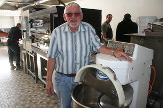 """Reinhold Rees, ehrenamtlicher Chef des """"Rührwerks"""", vor einer namensgebenden Maschine in der ehemaligen Kantinenküche, die weiter jeden Donnerstag Pizza- und Nudelteig knetet."""