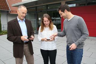 Beim Probelauf testen Bürgermeister Wolfgang Reinholz, Jennifer Abele und Hauptamtsleiter Daniel Retsch die neue App.
