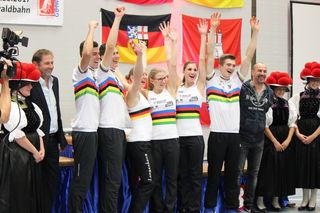 Glückliche German Masters Sieger umrahmt von den Gutacher Bollenhutträgerinnen.