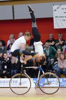Juliane Hauer im Kopfstand mit Madlen Schätzle in der Lenkerstützgrätsche auf einem Rad