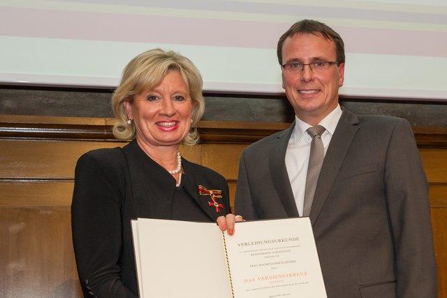 Im Auftrag des Bundespräsidenten überreicht Volker Schebesta Mauritia Mack das Bundesverdienstkreuz am Bande.