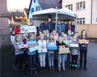 Uwe Köhler (hinten links) und Martin Baier (daneben) nahmen die Geschenke der Grundschulkinder aus Lahr-Sulz in Empfang. Stellvertretend durften Dritt- und Viertklässler den Geschenkeberg bestaunen.