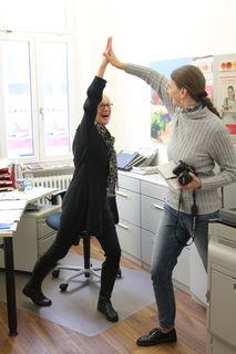 """Wenn Christina Großheim als rasende Reporterin unterwegs ist, hält in der Geschäftsstelle Kehl Marianne Büchel aus der Verwaltung die Stellung, auch in der Redaktion. So toll die beiden zusammenarbeiten, an ihrem """"give me five"""" müssen sie noch feilen. Sie tanzen hier nämlich nicht Pas de deux, sondern klatschen sich gerade ab. Auf der anderen Seite: Wer vermisst bei so viel herzerfrischender Kollegialität schon Coolness!"""