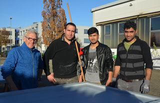 Projektbetreuer Klaus Scheuer (ganz links) mit drei von vier jungen Männern, die die Weihnachtsmarkthütten streichen (von links): Basil Yunis, Mahmoud Ahmadi und Fares Mousa.