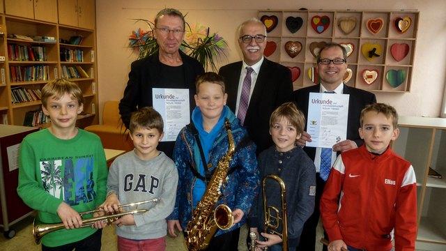 Toni Vetrano, Präsident des Blasmusikverbands Ortenau (hinten Mitte) überreichte der Weingartenschule in Zell-Weierbach und dem Musikverein Zell-Weierbach die Urkunde über die Musikpatenschaft.