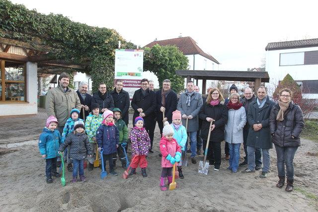 Kinder, Erzieherinnen, Elternbeiräte, Stadträte, Bürgermeister und Architekt nahmen gemeinsam den ersten Spatenstich für die Kindergartenerweiterung vor.