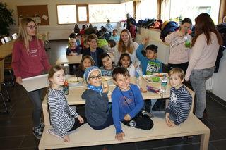 Katrin Knapp und JenifferSchmid (Bildmitte links und rechts) mit Juniorbegleitern und Grundschülern in der Mensa.
