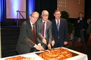 Der Straßburger Oberbürgermeister Roland Ries, Oberbürgermeister Toni Vetrano und Robert Herrmann, Präsident der Eurométropole de Strasbourg, beim Anschneiden der Neujahrsbrezel