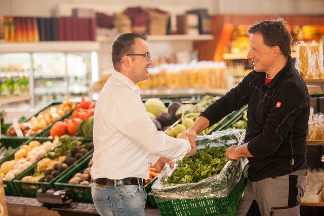 """Raiffeisen Kinzigtal Martkleiter Martin Isenmann (links) gemeinsam mit dem """"Grüne Theke""""-Landwirt Stefan Futterer."""
