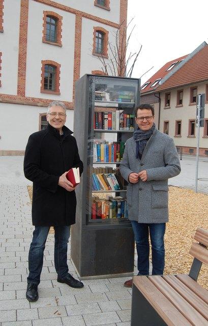 Syna-Kommunalberater Stefan Müller (links) und Willstätts Bürgermeister Marco Steffens nehmen den offenen Bücherschrank in Augenschein.