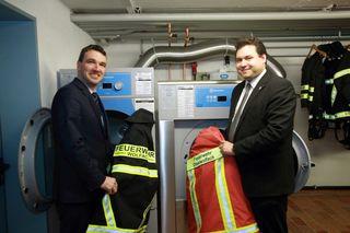 Die Bürgermeister von Wolfach und Oberwolfach, Thomas Geppert (links) und Matthias Bauernfeind, bestücken die neuen Geräte mit der ersten Wäsche.