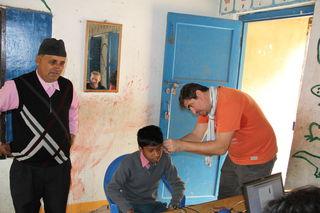 Michael Jung passt einem Jungen in einer Schule in Nepal sein erstes Hörgerät an.