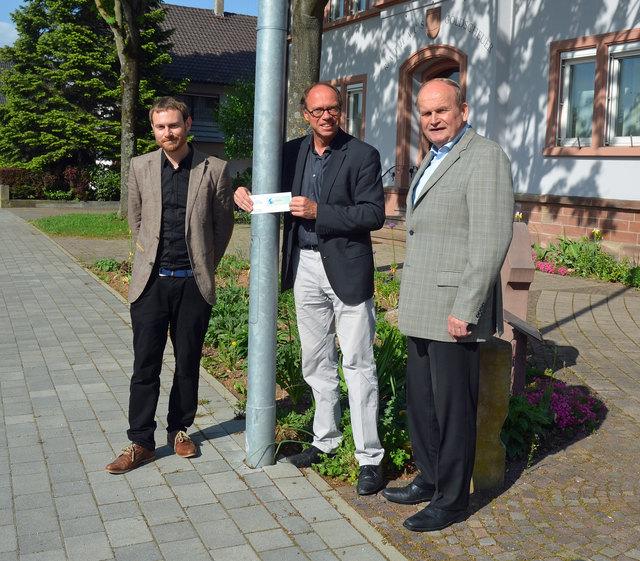 von links: Baubürgermeister Harald Krapp, Michael Görlitz vom städtischen Bereich Tiefbau und Ortsvorsteher Richard Schüler bringen in Marlen gemeinsam einen Nachweis für die Förderung des Bundesumweltministeriums für Umwelt, Naturschutz und nukleare Sicherheit an die neuen LED-Lampen an.